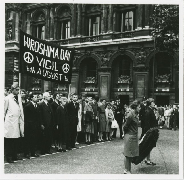 "Russell continued his role as a political campaigner well into his eighties. Here he is depicted (below banner, with wife Edith to the right) at a march for nuclear disarmament on ""Hiroshima Day Vigil, 6 August 1961"". Following the march and speech he gave that day, Russell and Edith served seven days in prison for refusing to keep the peace. (Image courtesy: McMaster University Libraries)."
